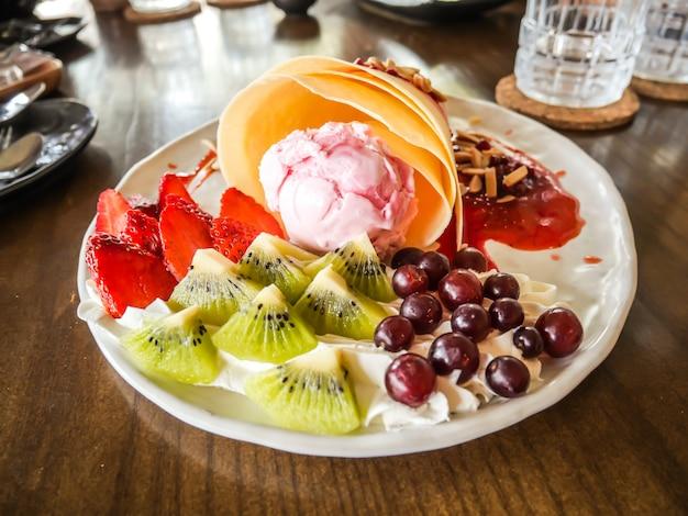 Вкусные вкусные домашние блинчики с мороженым клубничный, блины заполнены с клубникой, киви, виноград Premium Фотографии