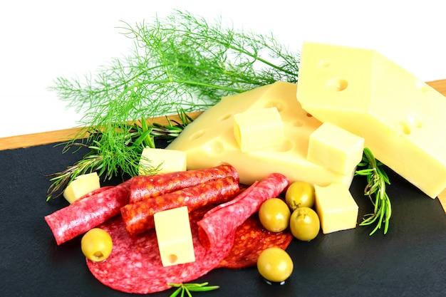 Ассорти из сосисок, сыра эмменталь, маслин и зелени на доске черных тапас. Premium Фотографии