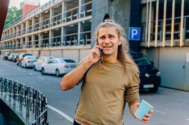 魅力的なスタイリッシュな流行に敏感な男は、紙コップからコーヒーを飲み、スーパーマーケットの近くの駐車場で電話で話しています。 Premium写真