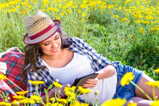 Девушка читает планшет на природе Premium Фотографии