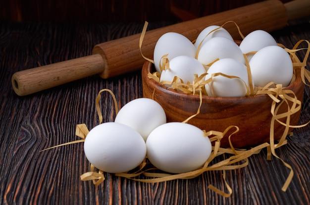 Белые яйца в деревянной миске, на бумажной соломе и деревянный стол. на обратной стороне скалки. низкий ключ. Premium Фотографии