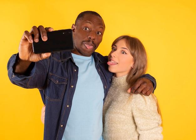 面白い自撮り。陽気な異人種間のカップルが顔をゆがめ、スマートフォンで写真を撮りながら舌を見せたり、ポーズをとったり、 Premium写真