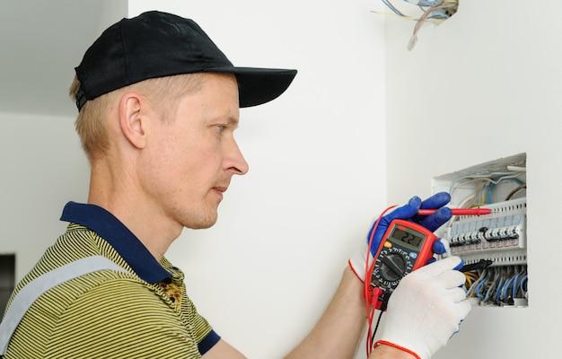電気技師は電気ヒューズボックスの電圧を確認します。 Premium写真