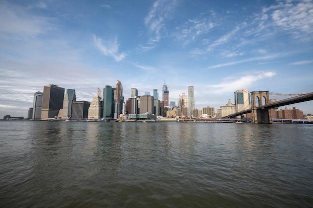 白昼のブルックリン橋でハドソン川のニューヨークのスカイライン反射 Premium写真