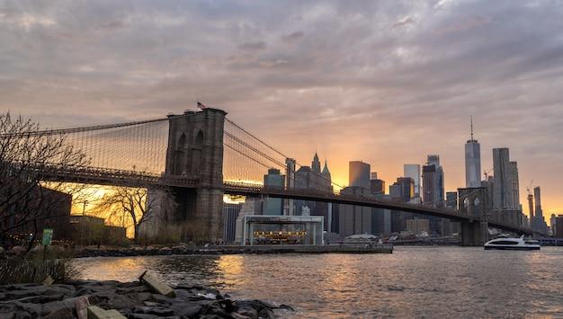 日没時のブルックリン橋でハドソン川にニューヨークのスカイライン反射 Premium写真