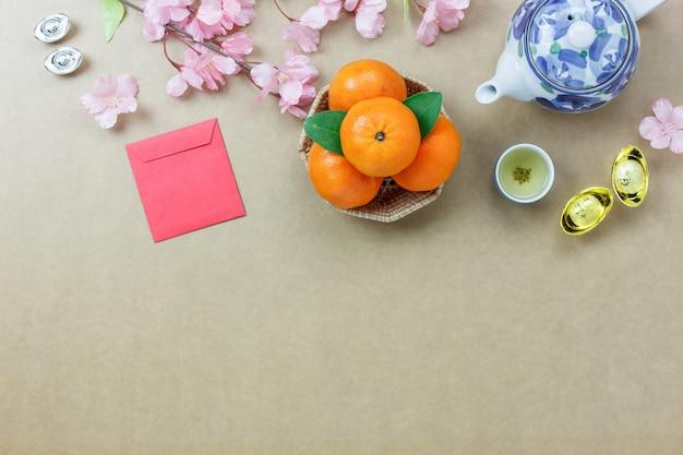 Верхний вид основных предметов первой необходимости счастливые китайские новые годы. другой язык означает богатый или богатый и счастливый. смешайте несколько предметов на современном сером деревянном столе для домашнего офиса. свободное пространство для дизайнов. Premium Фотографии