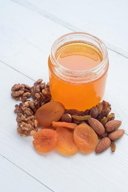 Мед, миндаль, грецкие орехи и курага. сушеные фрукты, лежа на белом деревянном столе. Premium Фотографии