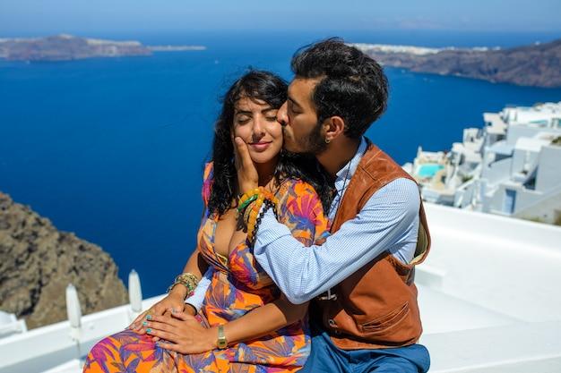Мужчина и женщина целуются у скалы скарос на острове санторини. деревня имеровигли. он этнический цыган. она израильтянка. Premium Фотографии