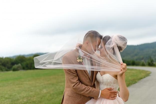 新郎新婦はベールの下で抱擁し、そっと頭を下げました。 Premium写真