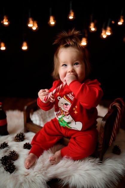 Милая девочка в красном новогоднем костюме с гирляндами в стиле ретро сидит на меху Premium Фотографии