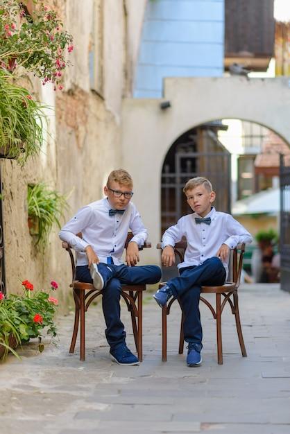 Две милые мальчики разговаривают сидя на деревянных стульях. мальчики подражают родителям бизнесменам. мальчики сидят на стульях, скрестив ноги с задумчивыми лицами. Premium Фотографии