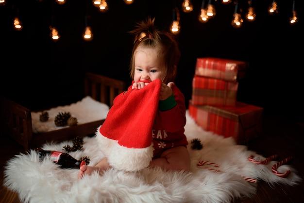 Девочка в красном новогоднем костюме с ретро-гирляндами сидит на меху Premium Фотографии