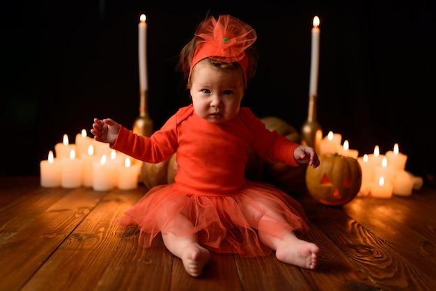 Маленькая девочка сидит с тыквами и свечами Premium Фотографии