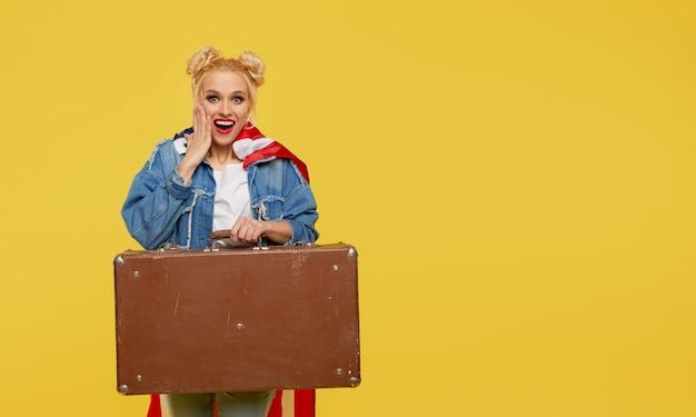 Молодая женщина с американским флагом держит в руках дорожный чемодан и денежные купюры. удивленное веселое лицо. Premium Фотографии