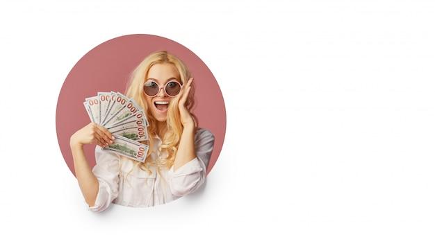 Портрет молодой женщины в шоке с пачкой банкнот и текст продажа. подглядывание через белую дыру в стене смешное лицо с открытым ртом. вау концепция Premium Фотографии