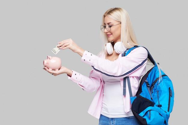 Стоимость обучения в колледже. портрет подчеркнул женщина с копилкой в руках. студент, имеющие проблемы с оплатой академической университетской степени обучения концепции. выражения лица. нейтральное серое пространство Premium Фотографии