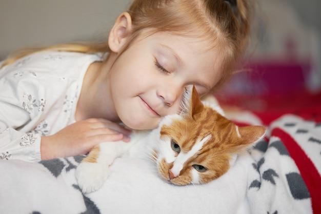 優しさと愛で赤毛の猫を抱きしめ、幸せで笑顔のかわいい子少女の肖像画 Premium写真