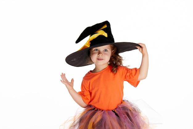 Смешная детская девочка в костюме ведьмы для хэллоуина на белом Premium Фотографии