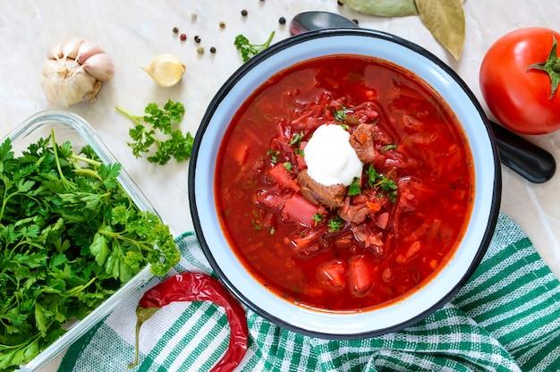 ボルシチは、テーブルの上のボウルに入った伝統的なウクライナ料理です。美味しくヘルシーなランチ。平面図、フラットレイアウト。 Premium写真