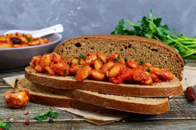 Кусок ржаного хлеба с фасолью. тушеная фасоль в томатном соусе с травами и специями на столе. постное меню. веганское блюдо. Premium Фотографии