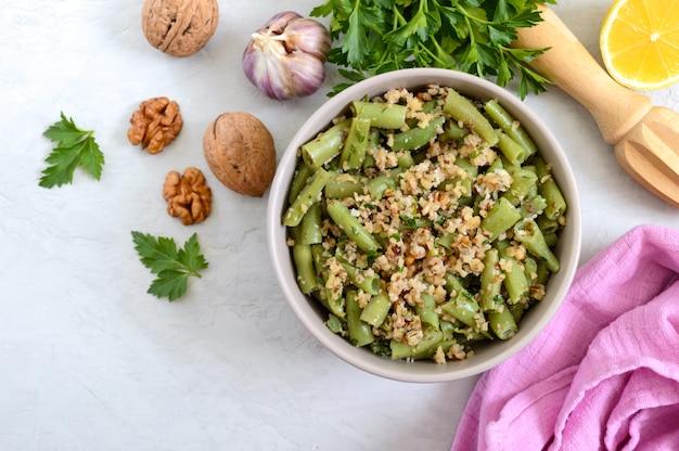 Салат с зеленой фасолью и острым ореховым соусом в миске. вегетарианское, веганское меню. вид сверху. Premium Фотографии