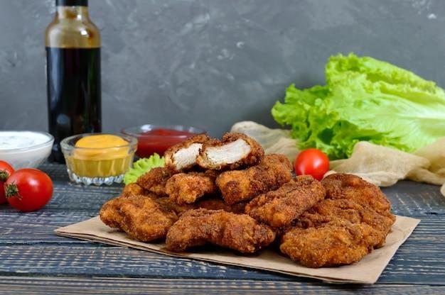 Куриные наггетсы. кусочки жареного хрустящего мяса, на бумаге с различными соусами на деревянном столе. традиционная закуска. Premium Фотографии