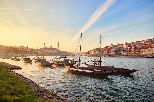 典型的なポルトガルの木造船、「バルコスラベロス」と呼ばれ、ドウロ川沿いのワイン樽を運んで、ポルト、ポルトガルのヴィラノヴァデガイアを望む Premium写真