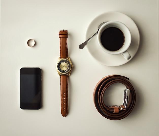 Мужские аксессуары, аксессуары для бизнесменов, набор прикольных мужских вещей, аксессуары для жениха, телефон, ремень, кольцо, часы, чашка кофе на столе Premium Фотографии