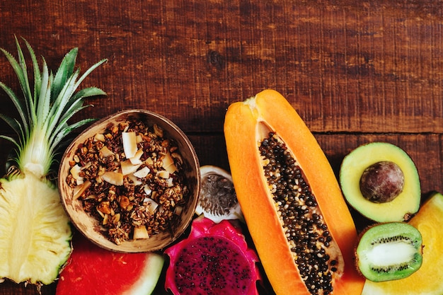 熱帯の新鮮な夏の果物と茶色の木製の背景にグラノーラの種 Premium写真