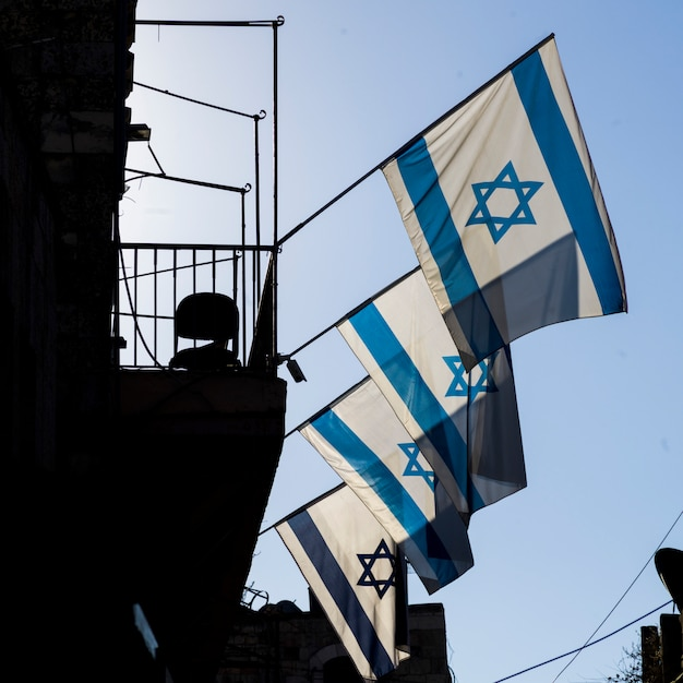 エルサレム、イスラエルの旧市街にある建物のイスラエル国旗の低角度図 Premium写真