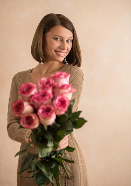彼女の腕に花の大きな花束を持つ美しい女性 Premium写真