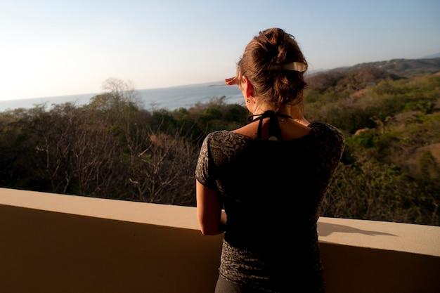 バルコニーからの水平線上の丘の上を見下ろす女性のリアビュー Premium写真