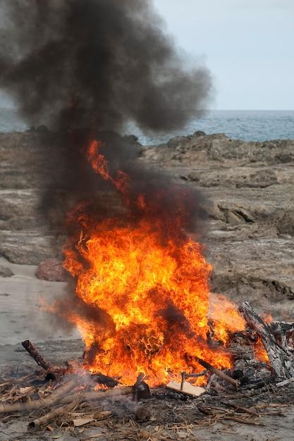 ビーチで激しく煙を燃やす赤い焚き火 Premium写真