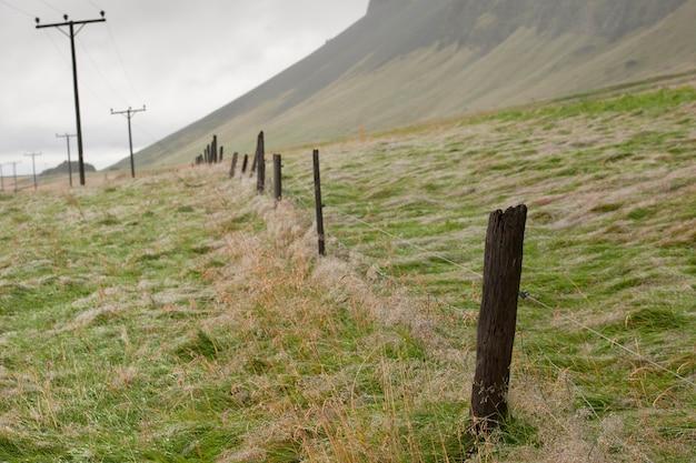 牧草地の丘の上で消える電柱と有刺鉄線のフェンスのポスト Premium写真