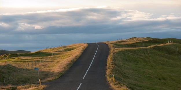 風景、高速道路、農地を通って地平線上に曇った日に消えていく Premium写真