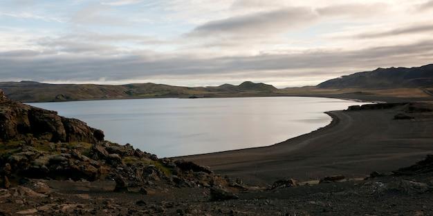 火山性の黒い砂と岩の丘がある穏やかな湖 Premium写真