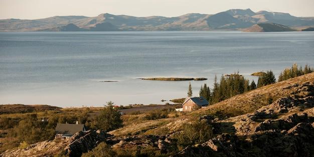 落ち着いた水の体と遠くの山々との険しい丘の上の住宅 Premium写真