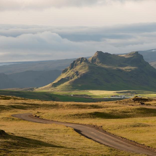 アイスランドの草原を通って山々に向かって消えていくハイウェー Premium写真