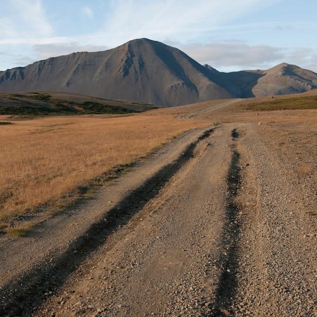 山につながる砂利道の轍 Premium写真