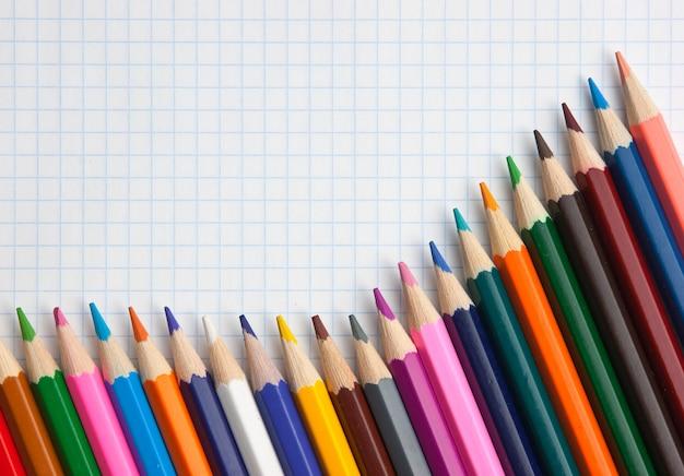 Цветные карандаши в школьной тетради Premium Фотографии