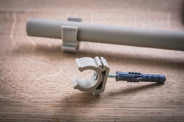 木の板のクリップが付いているポリプロピレンの固定器そして管 Premium写真