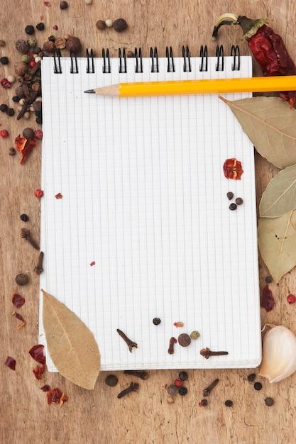 Блокнот для рецептов и специй на старом деревянном столе Premium Фотографии