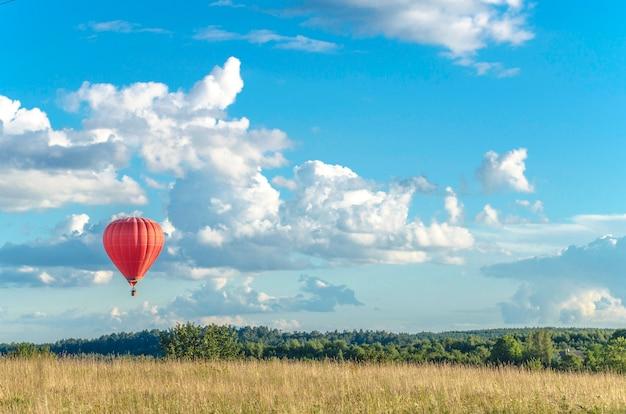 赤い飛行機の風船が雲と青空の地平線上を遠くに飛んでいます Premium写真