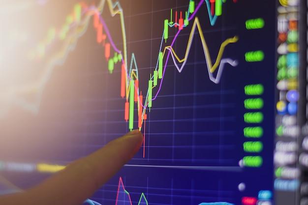 Палец, указывающий на биржевой график Premium Фотографии