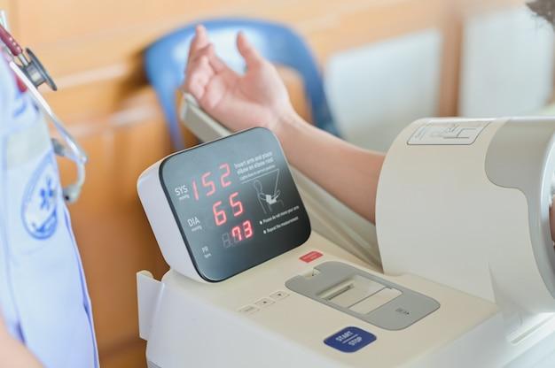 血圧計は、病院の患者の血圧をチェックする高血圧または高血圧を表示します。 Premium写真