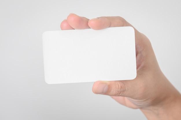 空のビジネスカードは、ぼんやりしたオフィスデスクの背景に手を携 Premium写真