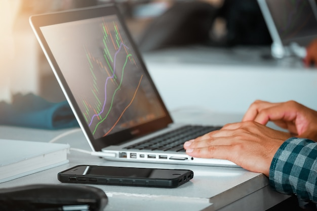 Крупный план человек, используя ноутбук фондовый рынок рынка кофе кафе Premium Фотографии