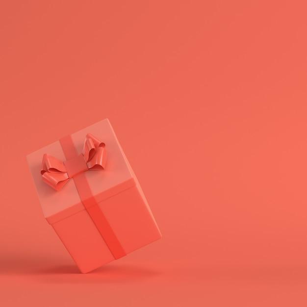 生きている珊瑚色の弓が付いているギフト用の箱。ミニマリズムのコンセプト Premium写真