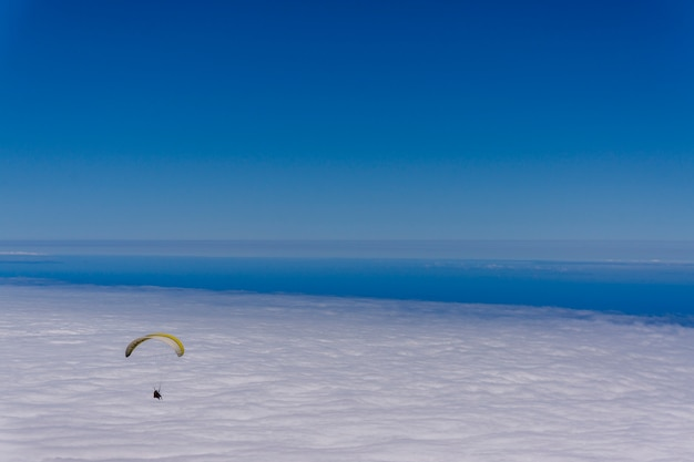 Параглайдинг над морем облаков в небе в ясный солнечный день Premium Фотографии