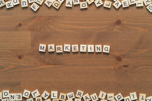 マーケティングテキストは、木製のオフィスの机に分離されたスクラブル文字で書きました。背景テンプレート。 Premium写真